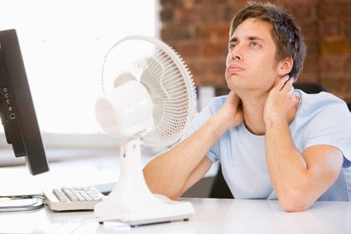 Businessman-in-hot-office-with-computer-and-fan-cooling-off