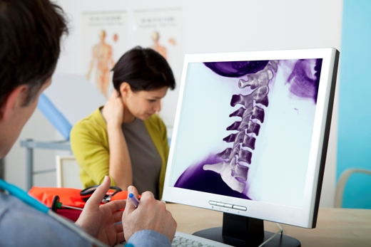 Models. On screen, colorized x-ray of cervical vertebrae.