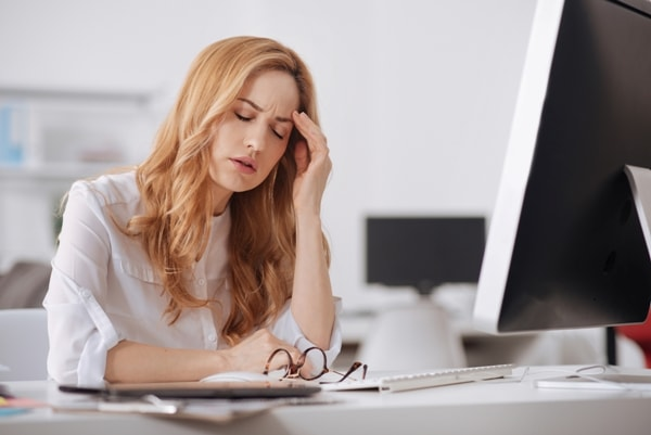 woman-with-headache-in-front-of-computer